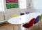 Lokale indrettet med farverig stole og kunst